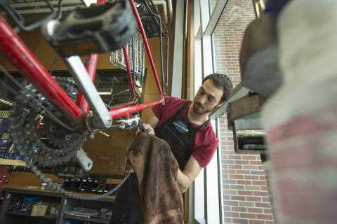 Paul Gebers, a student employee at the Outdoor Adventures Center bike shop, works on a chain as part of a basic bike tune-up.