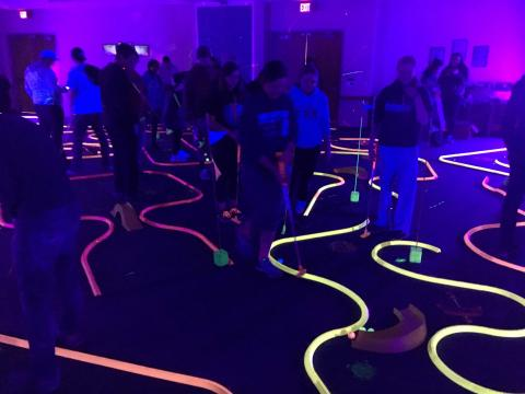 Students play glow golf under black lights in the Nebraska Union